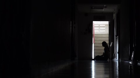 Silhouette of a sad young girl sitting in the dark leaning against the wall in old condo, Domestic violence, family problems, Stress, violence, The concept of depression and suicide.