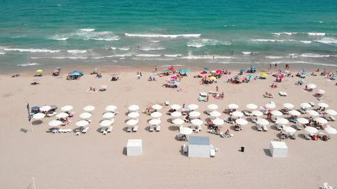 Aerial footage of the beach umbrellas and surf board rental at Alicante Beach,ing sideways