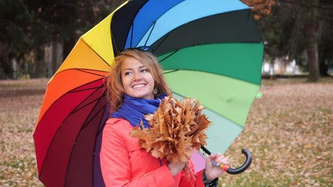 Happy cute longhaired blonde woman with a large colourful spinning umbrella in a red coat in the autumn park turns around and smiles at the camera with yellow maple leaves in her hand.