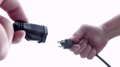 Man's hands plug in and unplug end of extension cord