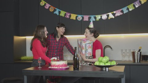Loving mom and best friend giving gift boxes to surprised birthday girl in cone hat laughing while taking presents from close people. Cheerful women enjoying festive event celebration in kitchen.