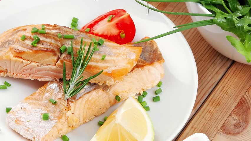 healthy fish cuisine : grilled pink salmon steaks with red caviar in white bowl lemon and vegetable salad dish with cutlery and pepper grinder over wooden table 1920x1080 intro motion slow hidef hd