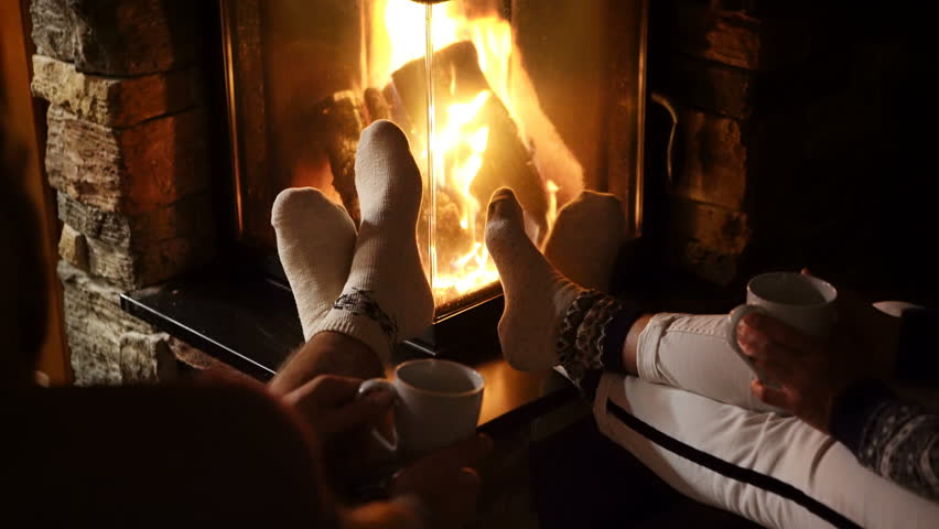 4K Couple seating near fireplace stretching their legs having warm beverages. Wearing Christmas socks.