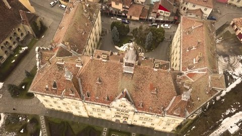 A drone shot, with orthomosaic framing and downward motion with pan, capturing a glimpse of a vintage architechture, of a closed locality, in the city of Sighisoara on an afternoon