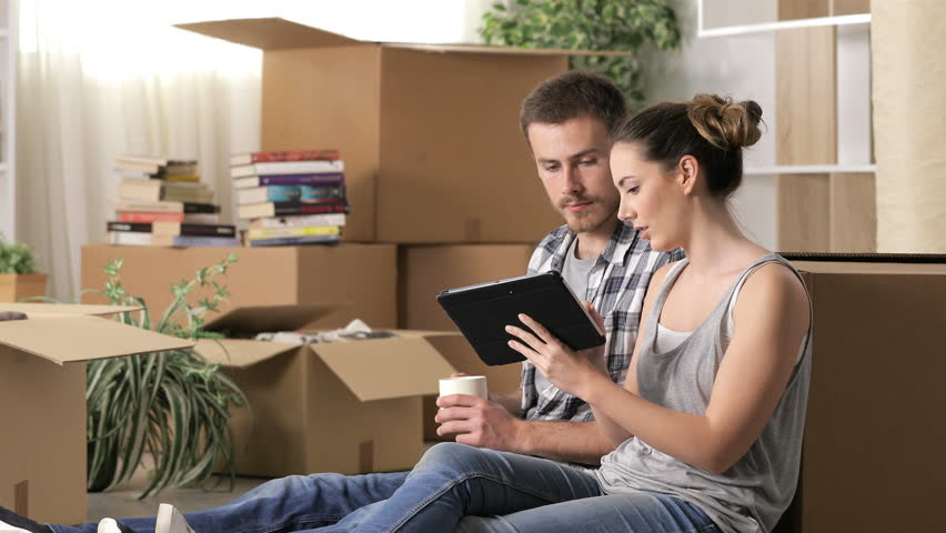 Happy couple moving home using a tablet to plan reforms sitting on the floor