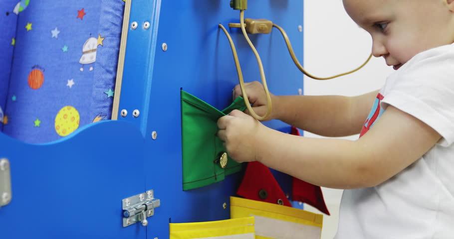 A little boy plays with his busycar. Montessori educational toy. Fine motor skills. Sensory sensitivity.   Shutterstock HD Video #1027889990