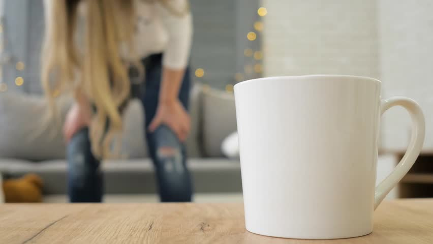 A young girl is trying to wear jeans.   Shutterstock HD Video #1027931300