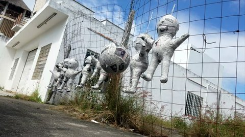Paper Mache Mexican Pinata Dolls Toys Hanging On A Fence In Mexico Blowing In The Wind