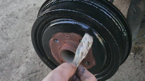 Man paints in black color rust brake caliper before replacing the wheel.