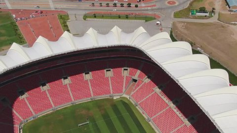 Port Elizabeth, South Africa - circa 2010s: Close view of Nelson Mandela Bay Stadium seats and green grass pitch with lawnmower. Aerial pull back and tilt up to reveal some traffic on nearby roads