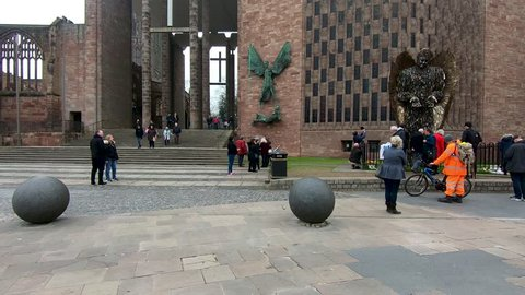 Coventry, West Midlands, UK - April 7, 2019: Time lapse of people looking and taking photographs of a statue outside Coventry cathedral