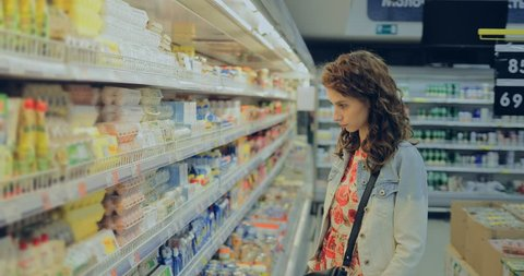 Young woman chooses eggs at the grocery store. Girl takes a cassette of eggs and puts it in the cart.