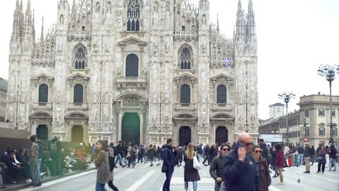 MILAN, ITALY - APRIL 12 2019:  Crowd of people and tourists in Milan, Italy, by the cathedral or dome, Duomo di Milano in spring. Tourism and holidays in the cities of Italy. Tilt up.