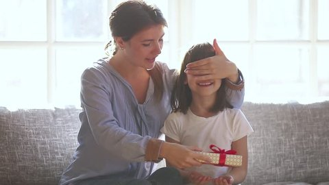 Loving mom make surprise closing eyes of cute child daughter give gift box embrace happy little girl, caring mother congratulate small kid with birthday prepare present on holiday hug sitting on sofa