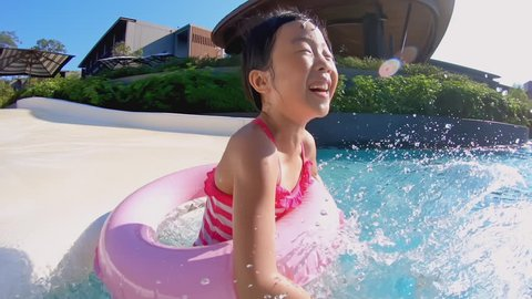 Happy little asian girl play water on waterslide of water park in summer sunny day