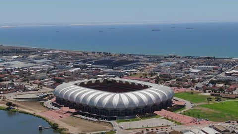 Port Elizabeth, South Africa - circa 2010s: Aerial hyperlapse, orbit around Nelson Mandela Bay Stadium on a sunny summer day. See harbour, industrial area, traffic come alive around the stadium.