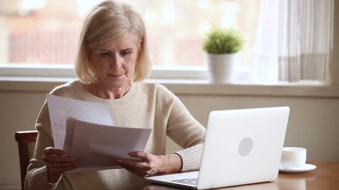 Elderly stressed woman sitting at table in kitchen at home holds domestic bills use laptop makes online payments feels concerned forgot to pay or debt formed, check finances financial problems concept