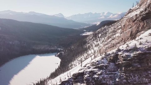 ARIEAL: 4K Drone shot of Lake and Canadian Rocky Mountains. Mountain Drone Ariel footage near Banff, Canmore, Jasper, Lake Louise, Canadian Rocky Mountains.