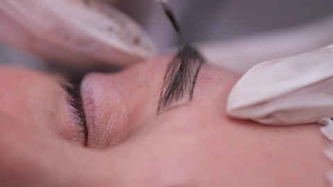 Close-up. Eyebrow, on which a specialist inject a needle and apply a pigment. Permanent makeup.