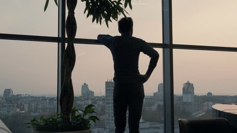 Silhouette Businessman Stands Near Tall Window In Office.Man Stand Near Window On Evening City.Businessman Stand Near The Panoramic Window. Business Man Walking And Stand Near Window In Modern Office.