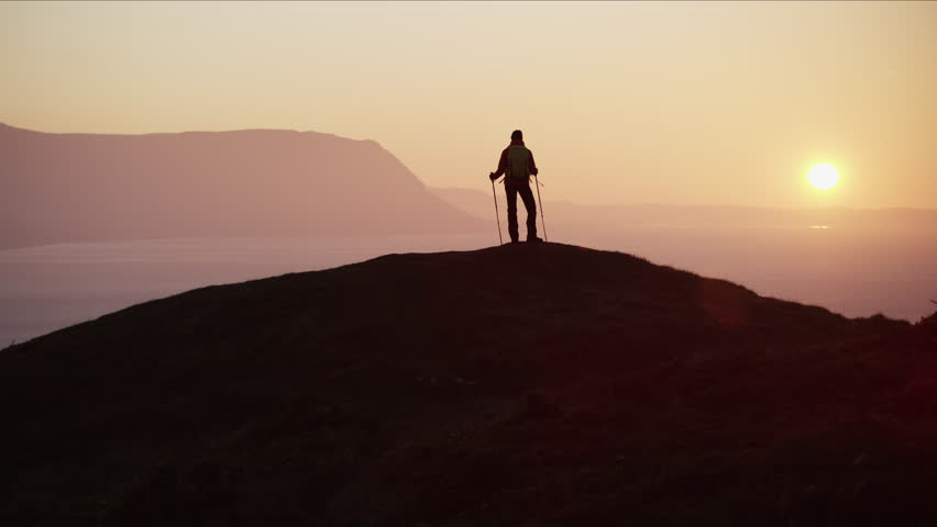 Silhouette of fit Caucasian European woman hiker Nordic walking mountains outdoors at sunrise Snowdonia National Park Wales United Kingdom RED MONSTRO #1028325680