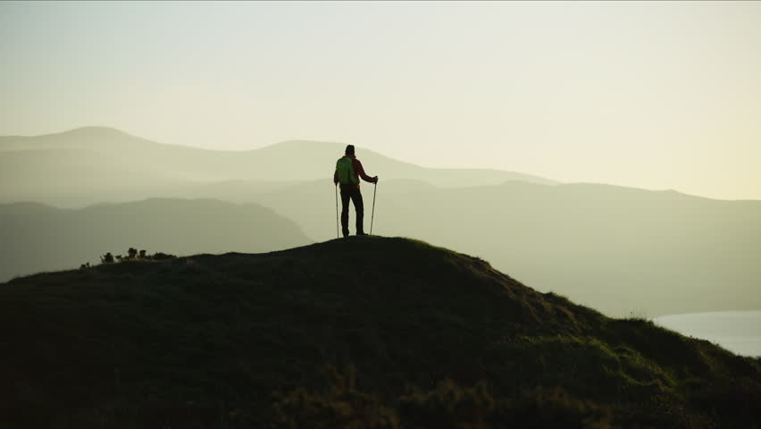 Silhouette of active Caucasian European female adventure hiker enjoying hiking on the top of mountain Snowdonia National Park Wales RED MONSTRO #1028326250