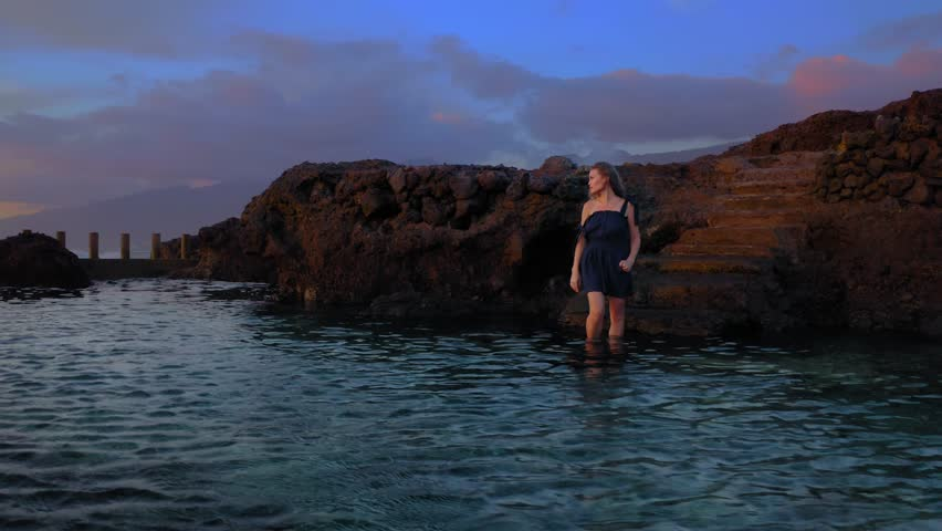 All Dreams come True in living Water. Young Woman Enjoys a Magnificent Sunset and Crystal Waters near the Volcanic Shore.