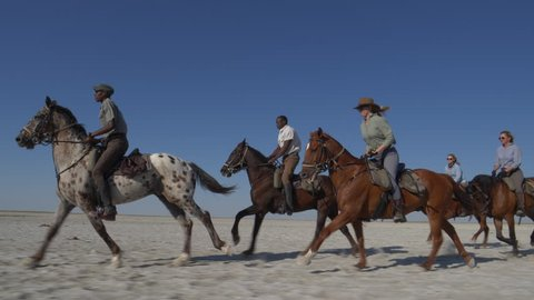 Slow motion view of a group of horse riders having fun galloping across the wide open spaces of the Makgadikgadi salt Pans