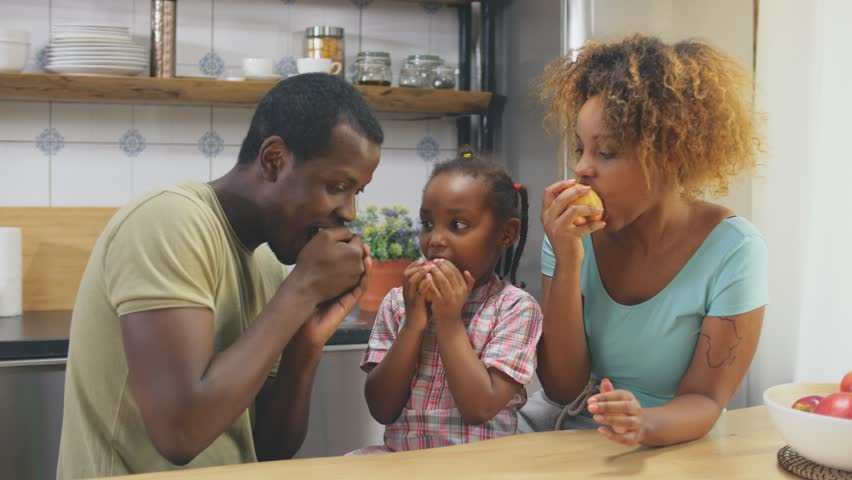 Happy young African American family eating apples together in kitchen. Healthy diet concept. | Shutterstock HD Video #1028372390