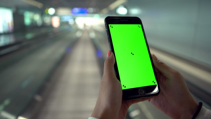 4K, Asian woman show the green screen phone on moving sidewalk at international airport. Using smartphone for one advertisement. Traveller in departure terminal for take the plane to travel-Dan