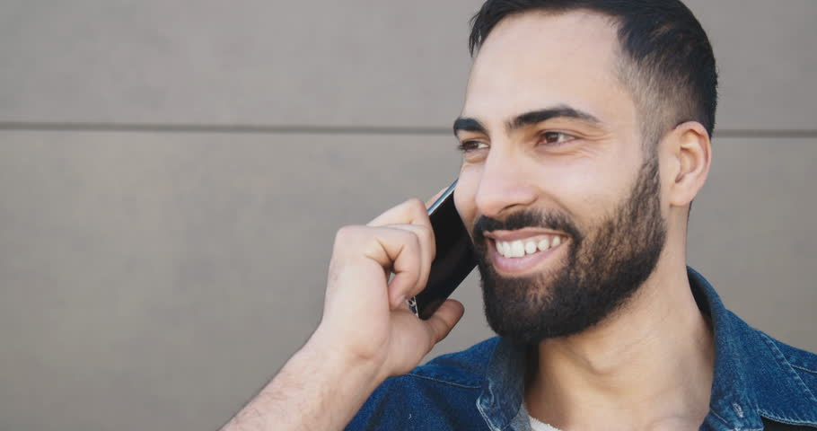 Close up of handsome bearded man dressed in denim jacket talking by smartphone before grey wall | Shutterstock HD Video #1028389280