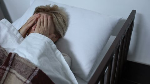 Elderly female patient massaging temples, suffering terrible migraine in sickbed