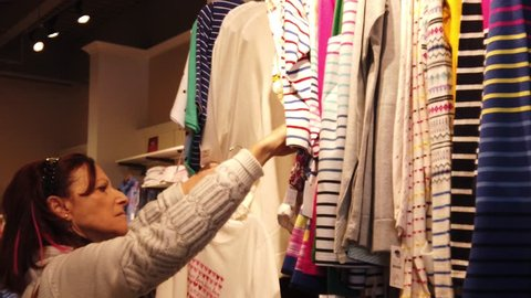 A Pretty mature woman is seen looking through a rack of striped blouses in a outlet clothing store