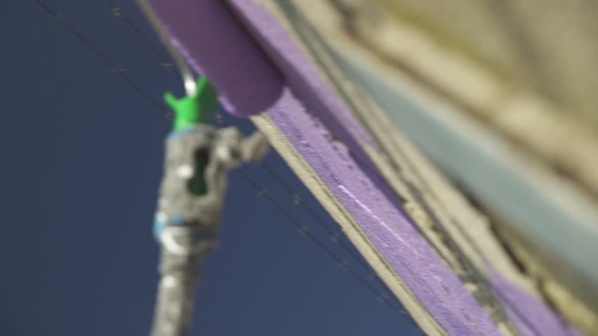 Painting a wall on the street with a purple paint roller 3