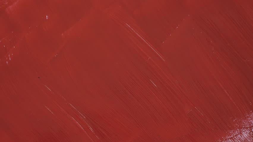 Laying a messy red paint brush on red painted surface close up #1028448590