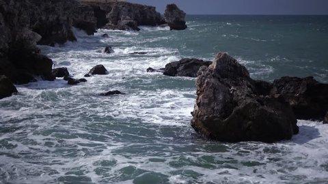Storm at sea. Big waves break on the rocky shore, white foam on the water. Black Sea, Bulgaria