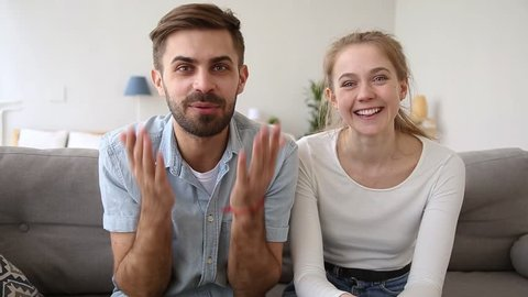 Overjoyed millennial vloggers record amusing video, couple sitting on couch chatting looking at web camera talking with friends online distance communication, wireless modern technology usage concept