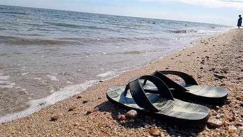 Flip-flops stand on the seashore, Flip-flops on the beach against the background of the sea Slow Motion