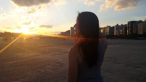carefree woman happy on the beach enjoying sunset on Santos Brazil