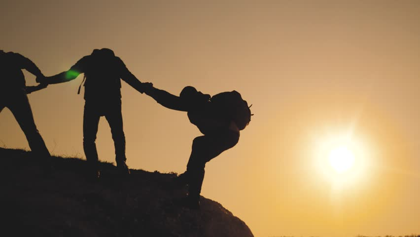 Teamwork help business travel lifestyle silhouette concept. group of tourists lends a helping hand climb the cliffs mountains. people climbers climb to the top overcoming hardships the path to victory | Shutterstock HD Video #1028575730