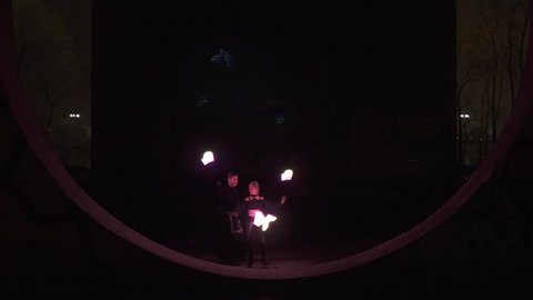Led and diode performance of the two artists man and woman at the night.