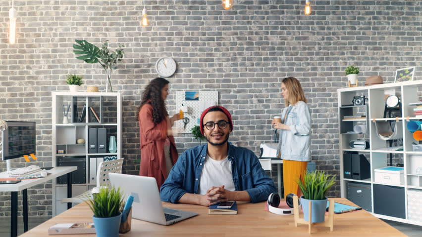 Zoom in time-lapse of happy business owner looking at camera and smiling sitting in office while men and women are moving around working. Millennials and job concept.