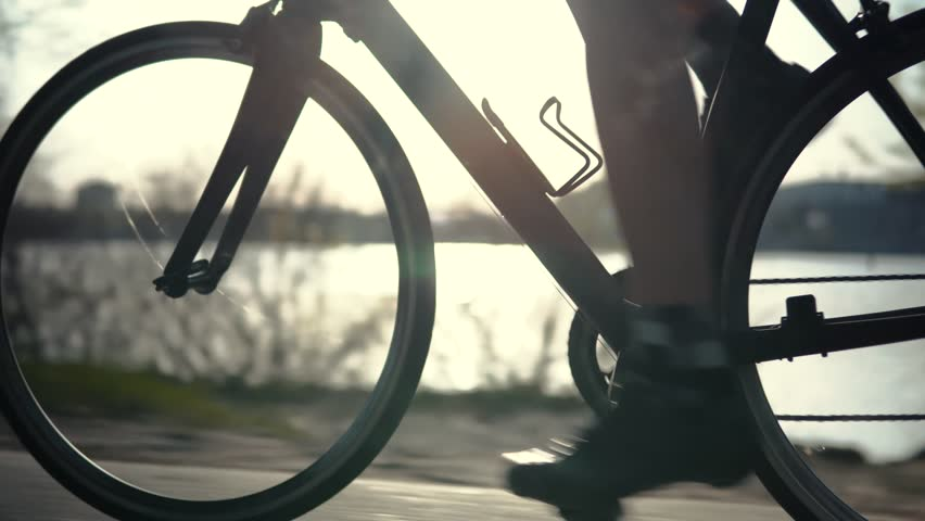 Cyclist Twists Pedals And Riding On Road Bicycle.Cycling Athlete At Sunset On City Park.Gear System Road Bicycle And Bike Wheel Rotation.Close-Up Cyclist Pedaling On City Park At Sunset.Sport Concept