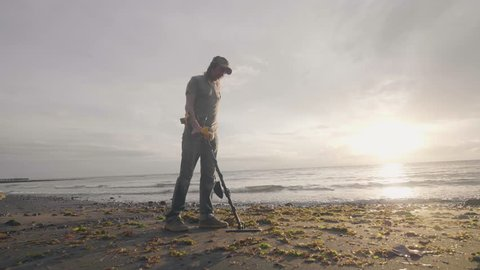 Man searching for valuables under the sand using a metal detector walking with his dog on tropical beach at sunrise.