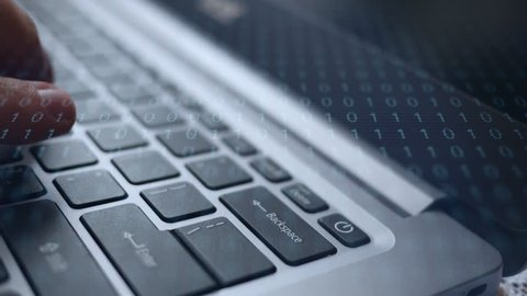 Finger dramatically presses the backspace button on laptop with binary overlay