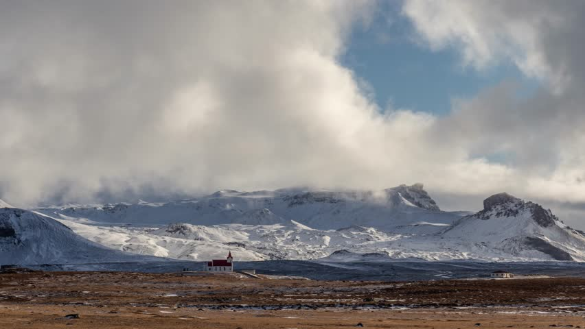 Timelapse of snow clouds above a church with epic mountains and mist in the background. Snaefellsnes peninsula, Iceland. #1028676440