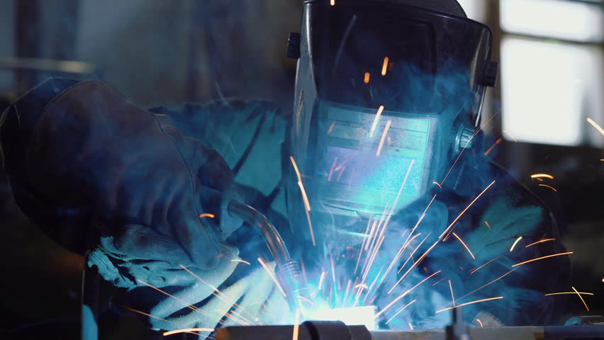 Close up: worker in face shield or protective mask uses gas welding torch to connect the seam of metal part in industrial factory. Blue fire flickers, orange sparks are flying, blacksmith manual work. | Shutterstock HD Video #1028686460