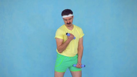 Funny young man trainer with a mustache from 80's is engaged with dumbbells