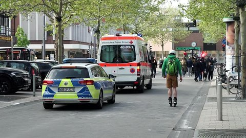 Wolfsburg, Germany, May 1, 2019: A Mercedes Benz van and a VW Passat police car are driving behind the May 1 demonstration.