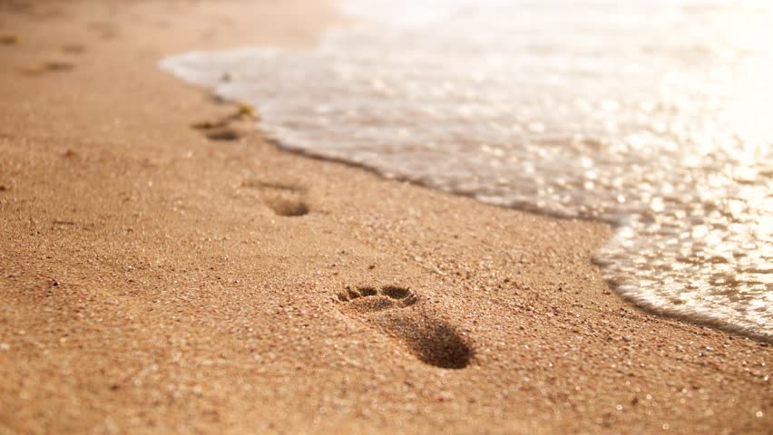 4k closeup footage of sea waves wahing off footprints on the golden sand at beach